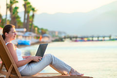 Girl with a laptop looking at the sea Royalty Free Stock Photos