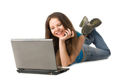 Girl with laptop lying on floor Stock Images