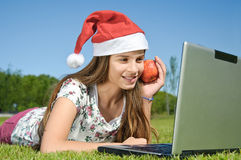 Girl with laptop lying on a grass Stock Images