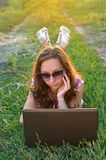 Girl with laptop lying on the grass Stock Photos