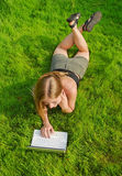 Girl with laptop lying on lawn Stock Photo