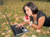 Girl with laptop lying on a leaves and eat apple Royalty Free Stock Photo