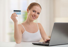 Girl with laptop makes payment online cards Royalty Free Stock Photos