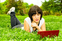 Girl with laptop on the meadow Stock Photography