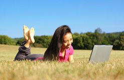 Girl on Laptop in Meadow. Fashionable girl working on laptop in a meadow stock image