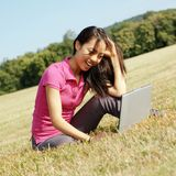 Girl on Laptop in Meadow. Fashionable girl working on laptop in a meadow stock photo
