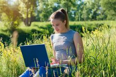 A girl with a laptop in nature among the green grass. royalty free stock photo