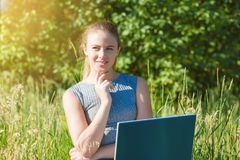 A girl with a laptop in nature among the green grass. stock photos