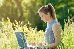 A girl with a laptop in nature among the green grass. stock photography