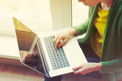 Girl with laptop near window stock photos
