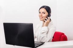Girl with a laptop in the office calling phone stock images
