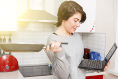 Girl with laptop and pan stock photography