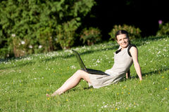 Girl with a laptop in a park. Girl with a laptop with wireless internet sits on the grass in the park and enjoys the sun and her friends online royalty free stock photos