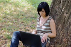Girl with a laptop in a park Royalty Free Stock Photography