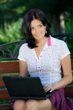 Girl with laptop in park Royalty Free Stock Photography