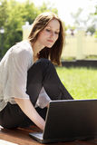 Girl with a laptop at park Stock Image