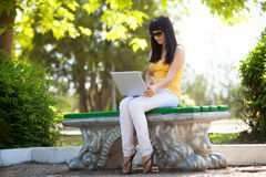Girl with laptop in the park Royalty Free Stock Photo
