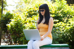 Girl with laptop in the park Royalty Free Stock Photos
