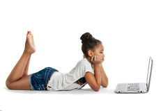 Girl with laptop. Pensive dark-skinned teen girl with a laptop. Girl lies royalty free stock photos