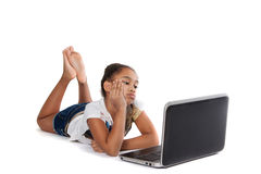 Girl with laptop. Pensive dark-skinned teen girl with a laptop. Girl lies stock image