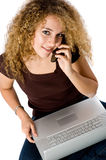 Girl On Laptop and phone. A young pretty woman with laptop computer and mobile phone on white background stock photo