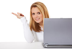 Girl with laptop points to the side Stock Images