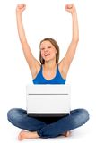 Girl with laptop raising her arms in joy. Young woman sitting on floor using laptop Royalty Free Stock Photos