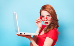Girl with laptop. Redhead girl with laptop on blue background royalty free stock image