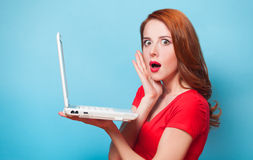 Girl with laptop. Redhead girl with laptop on blue background stock images