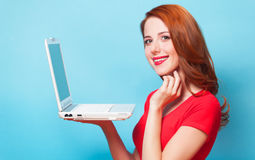 Girl with laptop. Redhead girl with laptop on blue background stock image
