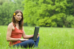 Girl with laptop relaxing on the grass, 'free comm Royalty Free Stock Images