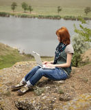 Girl with laptop at rock near lake and tree. Royalty Free Stock Photos