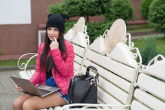The girl with the laptop. Sits on a bench and slipped a finger into her mouth Royalty Free Stock Photography