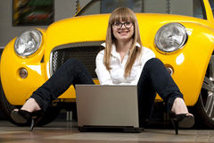 Girl with laptop sitting against of yellow car Royalty Free Stock Photos