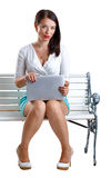 Girl with a laptop. Sitting on the bench isolated on white background Royalty Free Stock Photo