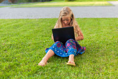 Girl with laptop. Girl is sitting on the grass with laptop Stock Photos