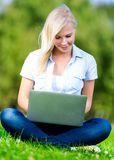 Girl with laptop sitting on the grass Royalty Free Stock Photo
