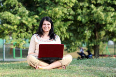 Girl with laptop sitting on grass Stock Photos