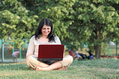Girl with laptop sitting on grass in park Royalty Free Stock Photography