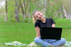 Girl with laptop sitting on the grass. Girl with a laptop sitting on grass writing in a social network emotionally royalty free stock photography