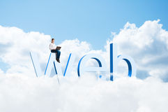 Girl with a laptop sitting on the letters WEB Stock Images