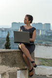 Girl with laptop sitting on open air Royalty Free Stock Photo