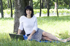 A girl with laptop sitting in a park Stock Photo