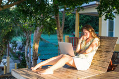 Girl with laptop sitting on the recliner in the outdoors near the house. Working. Stock Photos