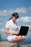 Girl with a laptop sitting on a stone Royalty Free Stock Photos