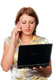 Girl with the laptop speaks by a mobile phone Royalty Free Stock Photo