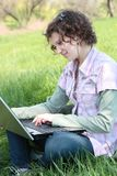 Girl with  laptop on the spring meadow Royalty Free Stock Images