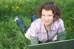 Girl with  laptop on the spring meadow Stock Photos