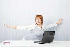 Girl with a laptop stretches in the workplace Stock Photo
