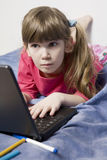 Girl with laptop surfing the net Stock Photography